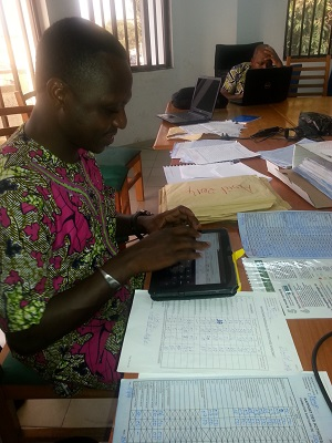 Logistician in Benin enters data on a tablet into OpenLMIS