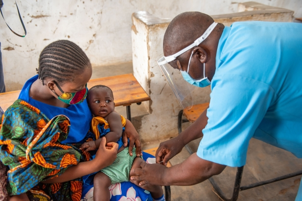 A Community Health Worker with PPE on vaccines a child.